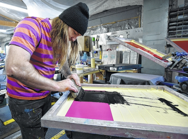 Tom Alper silk screens T-shirts manually at AxelRad in Wilkes-Barre. Aimee Dilger | Weekender