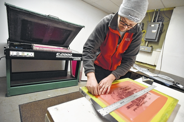 John Krispin squares up artwork to burn onto a silk screen at AxelRad in Wilkes-Barre. Aimee Dilger | Weekender