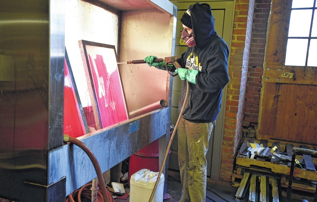 Nick Rishcoff washes away emulsion to reclaim silk screens at AxelRad. Aimee Dilger | Weekender