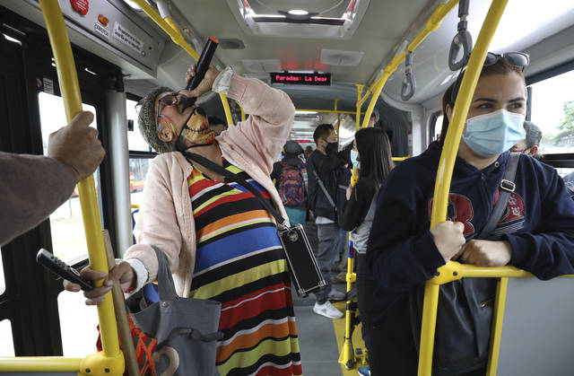 """<p>Marlene Alfonso, a 69-year-old Venezuelan grandmother who goes by the name """"Toothless Cindy,"""" sings about Venezuelan migrants' lives in hopes of tips from commuters on the Transmilenio, the crowded and crime-ridden public bus system in Bogota, Colombia, Tuesday, Nov. 3, 2020. Alfonso suffers from glaucoma and cannot see out of her left eye, thus can't see the buttons on her speaker's remote control properly, so she asks commuters for help to play the right tracks. (AP Photo/Fernando Vergara)</p>"""