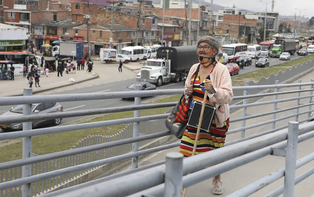 """<p>Marlene Alfonso, a 69-year-old Venezuelan grandmother who goes by """"Toothless Cindy,"""" walks up the ramp to enter the Transmilenio, the crowded and crime-ridden public bus system in Bogota, Colombia, Tuesday, Nov. 3, 2020. Alfonso says that she was already performing for tips in her hometown of Caracas, long before she arrived in Bogota, home to more than 350,000 Venezuelans. (AP Photo/Fernando Vergara)</p>"""